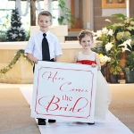 "Paying homage to one of the worlds most famed wedding sayings, our ""Here Comes the Bride"" Banner is a super fun and unique way to announce the brides arrival! Typically carried down the aisle by ring bearers and flower girls right before the bridal march, this ultra enjoyable banner will give all your guests one more reason to turn their heads in excitement! And because each sign can be customized in your choice of one of todays hottest wedding colors, its easy to see why so many brides are saying ""I do"" to this new trend! Custom banner comes complete with wooden dowel rod and two dowel caps for a truly distinctive, finishing look. Details: Size: Banner measures 27 inches wide by 24 inches long. Dowel rod measures 28 inches long. Materials: Poly canvas and wood"