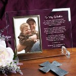 "Say Thank You to your Godfather with our attractive Personalized To My Godfather Picture Frame and besure to include your favorite photo of your little angel to complete this Engraved Godfather Keepsake. Our Personalized Godfather Beveled Glass Picture Frame is a heavy-weight glass with beveled edges on all sides, accented with golden brass frame trim. Frame measures 8"" x 11"" and holds your 4"" x 6"" photo; includes clear easel legs for top display. Includes FREE Personalization! Personalized with any two line custom message. (i.e. Forever In My Prayers/Love, Logan)"