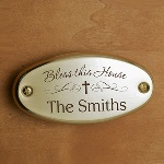"""This Bless This House door plate features pretty script with the phrase """"Bless This House"""" and a cross laser engraved on the plaque. This attractive housewarming gift idea can be customized with a family name or message, for a personalized housewarming gift. Each oval door plate measures 2 5/8"""" by 5 5/16"""", and makes a perfect gift for housewarming, whether a first home or a retirement dream come true. Surprise a favorite couple or new home buyers with this lovely brass door plate, an ideal housewarming gift!"""