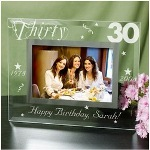 "Capture treasured memories of someone celebrating a milestone birthday with this beautiful Engraved Birthday Frame. Perfect for Mom, Dad, Family and Friends, this Personalized Birthday Frame is loved even after their special day has passed. Our Birthday Frame measures 9""x 7"" and holds a 3½"" x 5"" or 4"" x 6"" photo. Easel back allows for desk display. Includes FREE Personalization! Personalize your Happy Birthday Picture Frame with any age, birth year and milestone year, and any one line custom message. (i.e. Happy Birthday, Sarah!)"