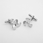 "Think out of the box with our dashing selection of cufflinks featuring designs that are a bit out of the ordinary. This pair of Propeller cufflinks comes packaged in an attractive personalized silver-tone case featuring the name of the recipient. These cufflinks make perfect groomsmen gifts and add a little pizzazz to any wedding attire. Light-weight plated polymer case measures 3"" x 1 1/8"" 1 1/2"" and is lined in black satin. Personalize the case with two lines of up to 15 characters per line."