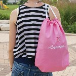 "Add a little style to your outfit with our Embroidered Icon Sports Pack. Every day trips to school, practice or vacation will be a breeze when you carry your essentials in this versatile Embroidered Name Sports Pack. Safely store your I-Pod, cellular phone or school materials with its convenient top loading drawstring closure during your day to day activities. Your 100% cotton Embroidered Sports Pack measures 18"" h x 14"" w with a drawstring top closure. Use this personalized sport pack instead of paper or plastic to help the planet. Personalized sports bags include FREE embroidery! Personalize your Embroidered Sports Pack with your choice of one of 5 back colors ( Red, Blue, Green, Pink, Lavender ), any name, choice between block or script lettering and choose your favorite icon (ie. Pink/ Lauren / Script / Ballet )"