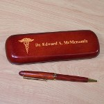 "Present your favorite doctor with a personalized doctor gift that is sure to be used every day. A Personalized Doctor Writing Set is an inexpensive doctor gift with an expensive feel. Each Rosewood Personalized Doctor Pen Set makes a unique Doctor gift for him or her. Personalized Pen Set for any doctor is presented with a matching rosewood case for convenient storage and a beautiful gift presentation. Pen measures 6"" in length, black ink and features twist action ballpoint operation. The pen can be refilled with a standard Parker refill. The Doctor Pen Case is personalized with any name."
