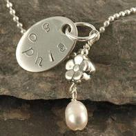 "A sweet little gift for the flower girl. Thick oval sterling silver disc with name stamped around the edge Sterling silver flower bead with freshwater pearl attached Includes 16"" sterling silver ball chain necklace This necklace is CPSIA compliant as shown Makes a great gift idea for a flower girl, special little godchild or daughter, niece or cousin."