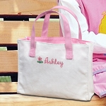 "Shell be pretty in pink with our Personalized Flower Girl Tote Bag. The fashion tote bags are constructed of white canvas, lined in pink cotton lining and feature sturdy pink leatherette handles. Her first name is embroidered for free on the front of the tote bag in pink thread, along with a pink and green flower. As a flower girl gift, the personalized tote bag is a great option for flower girls of any age. She can carry her wedding accessories to the wedding in her own personalized bag and then use the tote bag for years to come, as a book bag, school bag or even ballet bag. Details: Size: 9"" by 7"" by 2 inches Materials: Canvas and leatherette Embroidery Options: The Flower Girl Tote Bag can be embroidered with a scripted name (max of 15 characters) in pink thread at No Additional Cost."
