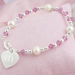 Your little one will absolutely love our Little Girls Heart Charm Bracelet. This delightful bracelet is adorned with sparkling clear and pink crystals, freshwater pearls and sterling silver-plated hardware. With all that dazzle shell be delighted to wear any chance she gets! Includes a free organza gift pouch. Details: Size: Measures 5 1/2 inches. Materials: Crystals, freshwater pearls and sterling silver-plated beading and charm Engraving Options: The Little Girls Heart Charm Bracelet may be engraved with her single initial in a cute lower case letter at No Additional Cost.
