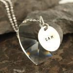 "Let her know that she has your heart with this personalized gift necklace. Personalize the item with your name. A HUGE crystal heart with a small silver disc added with the name of your choice up to 8 letters. Includes 18"" ball chain necklace in sterling silver."