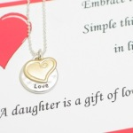 "Embrace the simple things in life... Card reads A daughter is a gift of love! Great to give to your daughter for a birthday, graduation or special celebration. Let her know just how much you love her. silver beaded ball chain with lobster clasp. Matt silver toned ""love"" disc and heart charm. Approximately 18"""