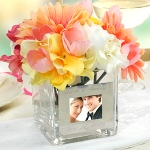 "Our Square Glass Vase with Photo Frame is a unique way to display your most prized picture. Because of its unique versatility, this dual frame and vase works great as a decorative centerpiece at wedding receptions, bridal showers, or even as a gift for a bridal party attendants. Bring them home and embellish everything from fireplace mantles to end tables with all your most cherished memories and decorations. Each table vase adds an exquisite decorative element to any special event and when the party is over it easily becomes a showpiece in your home for many years to come. Details: Size: Measures 4"" by 4"" by 4 inches. Materials: Clear glass and metal frame"